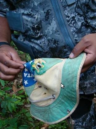 Integrante da Força Nacional segura chapéu de Nísio Gomes. Foto: Cimi/MS